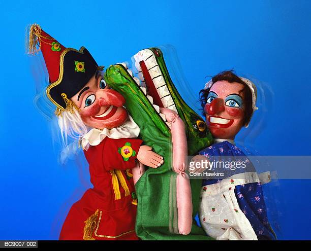 punch and judy puppets with crocodile character eating sausages - puppet show stock photos and pictures