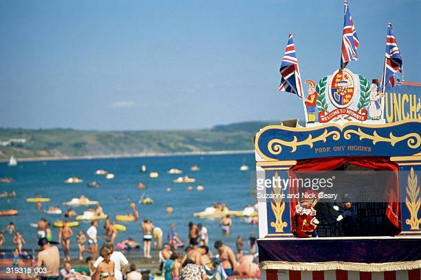 punch and judy show in progress, beach beyond,dorset,england - puppet show stock photos and pictures