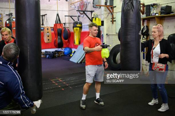 Punch bags are disinfected between training sessions at the Moss Side Fire Station Boxing Club in Manchester, northwest England, on July 25, 2020 as...