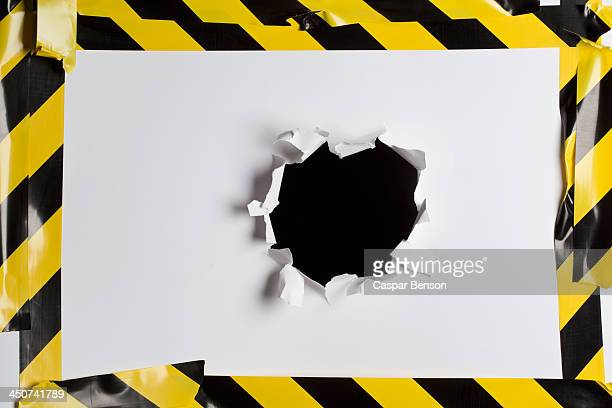 a punched out hole in cardboard with cordon tape around it - cordon boundary stock pictures, royalty-free photos & images
