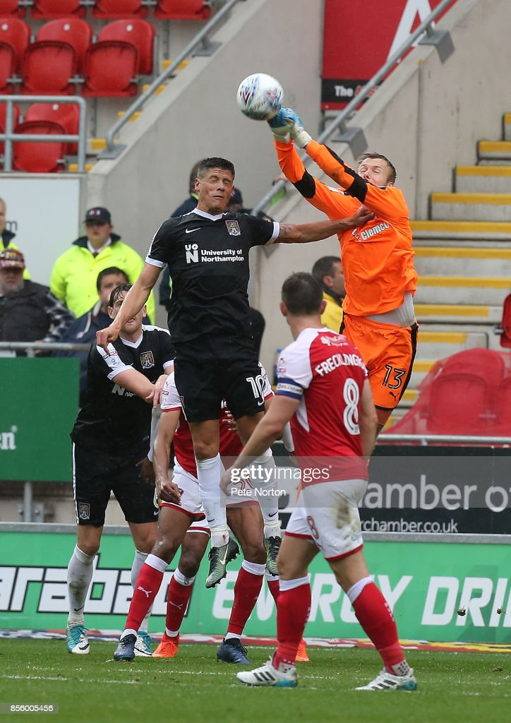 ROTHERHAM, ENGLAND - SEPTEMBER punches the ball clear under pressure from Alex Revell of Northampton Town during the Sky Bet League One match between Rotherham United and Northampton Town at The Aesseal New York Stadium on September 30, 2017 in Rotherham, England.