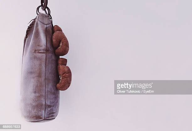 punching bag hanging with boxing gloves by white wall - boxing gloves stock photos and pictures