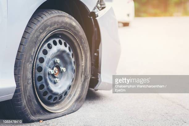 punctured car on road - puncturing stock pictures, royalty-free photos & images