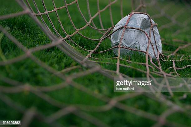 Punctured football laying abandoned in a goalmouth on a park football pitch in North Newington Oxfordshire UK