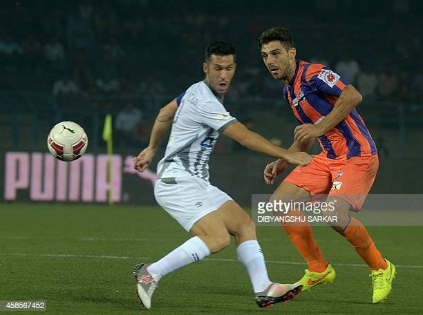 FC Pune City footballer Kostas Katsouranis and Atletico de Kolkata footballer Luis Garcia tussle for the ball during the Indian Super League football...