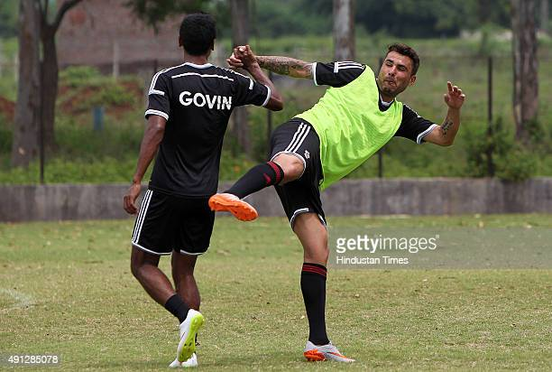 Pune City forward Adrian Mutu sharing some light moment with teammate Govin during the practice session on the eve of Indian Super League match...