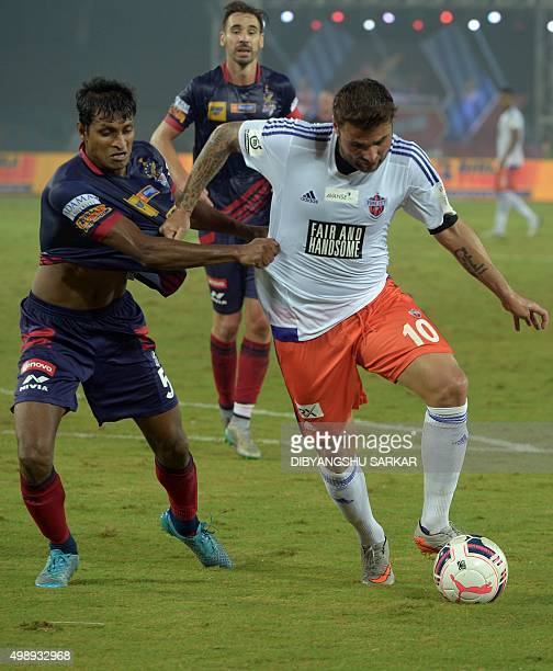 FC Pune City forward Adrian Mutu vies for the ball with AtleticodeKolkata's defender Arnab Mandal during the Indian Super League football match...