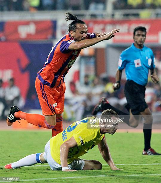 Pune City player Tuncay Sanli and Kerala Blasters FC player Peter Ramage in action during a match of Hero Indian Super League 2015 at Shree...