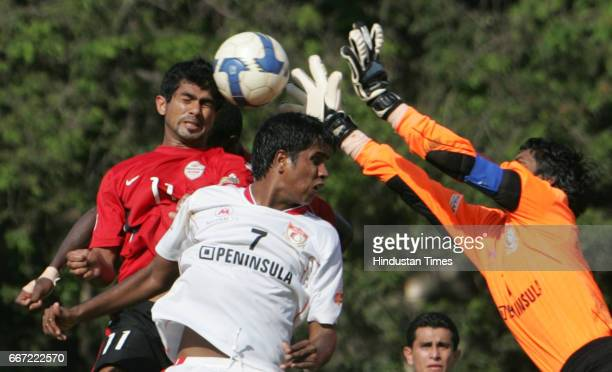 Pune FC goal keeper Subrata Paul and his teammate Kuttimani Sampath try to stop the header from Mahindra United's Mohd Rafi during their I League...