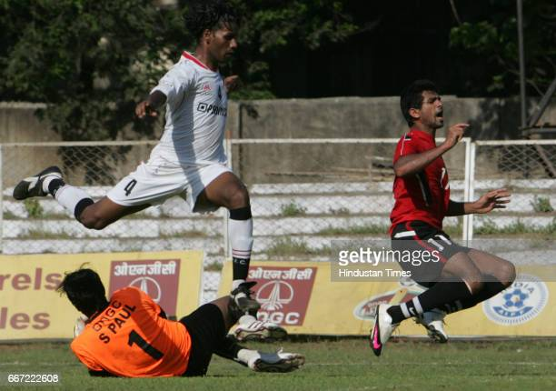 Pune FC goal keeper Subrata Paul and his teammate Selwyn Fernandes try to stop the kick from Mahindra United's Mohd Rafi during their I League...