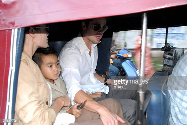 US actors Brad Pitt and Angelina Jolie sit with their son Maddox inside an Indian auto rickshaw as they take a tour of Pune some 200kms south of...