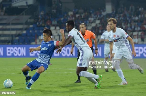 Pune players Rohit Kumar and Rafael Gomez Lopez look on as Bengaluru FC captain Sunil Chhetri kicks the ball during the Hero Indian Super League...