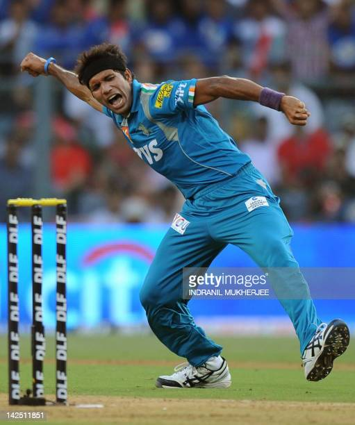 Pune Warriors India bowler celebrates after taking the wicket of Mumbai Indians batsman Rohit Sharma during the IPL Twenty20 cricket match between...