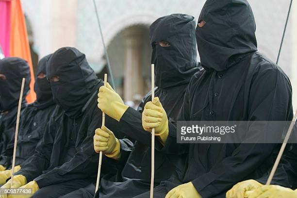 Punishers locally known as 'algojo' wait to whip the alleged sharia law offenders during the whipping punishment in front of public at Meulaboh on...
