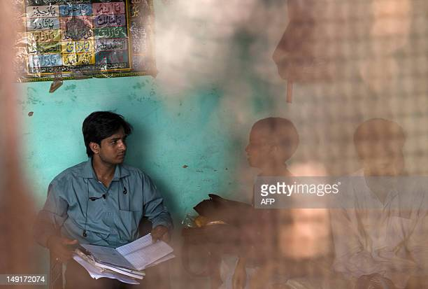 Punit a counsellor from the Indian NAZ foundation an NGO working to help HIV/AIDS patients speaks with an HIVinfected boy at his home in New Delhi on...