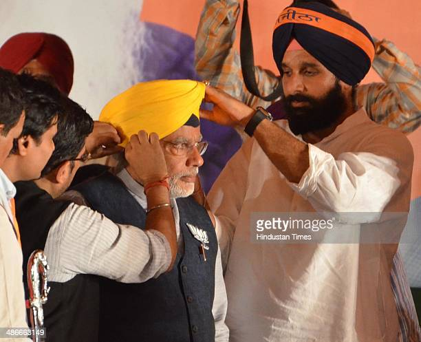 Punjab Cabinet Minister Bikram Singh Majithia tying turban on BJP Prime Ministerial candidate Narendra Modi during an election campaign rally in...