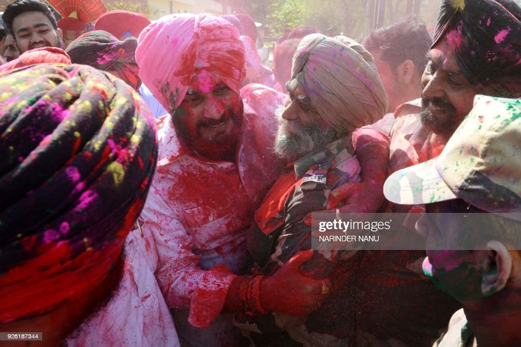 Punjab Cabinet Minister Navjot Singh Sidhu and Indian Border Security Force personnel celebrate the Holi festival smeared in coloured powder at the...
