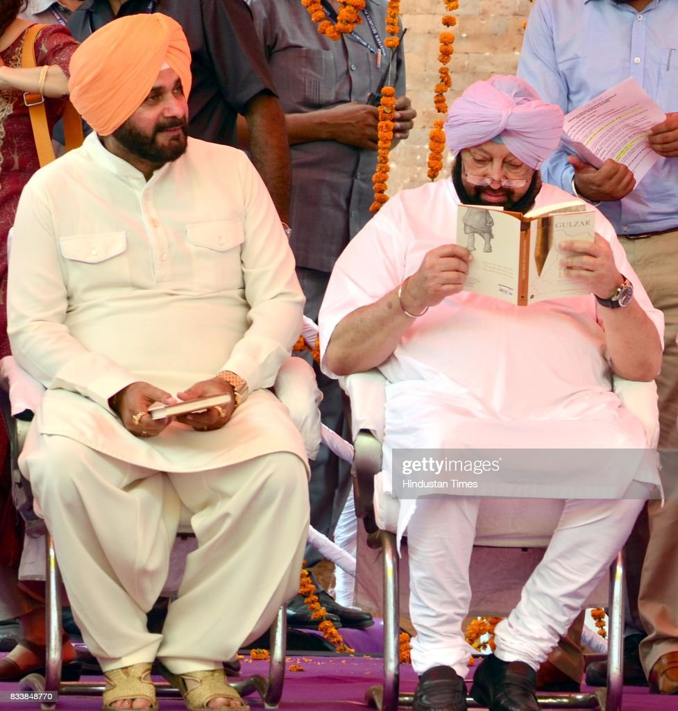 Punjab Chief Minister Captain Amarinder Singh reads the Gulzar book Footprints On Zero Line writing on Partition, while Punjab Local Bodies Minister Navjot Singh Sidhu (L) looks on, during the inauguration of Partition Museum at Town Hall, on August 17, 2017 in Amritsar, India.