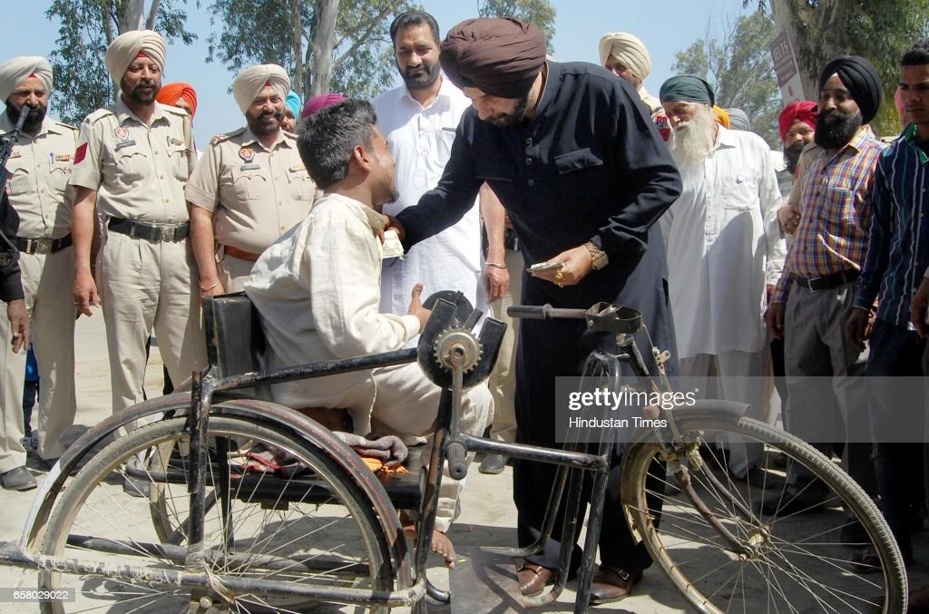 Punjab Local Bodies Minister Navjot Singh Sidhu helping a physically challenged man during the thanksgiving visit to his constituency at Village...