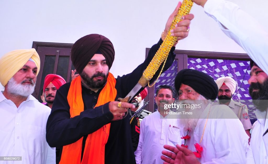 Punjab Local Bodies Minister Navjot Singh Sidhu offered a sword by party workers during the thanksgiving visit to his constituency at Village Mudhal..
