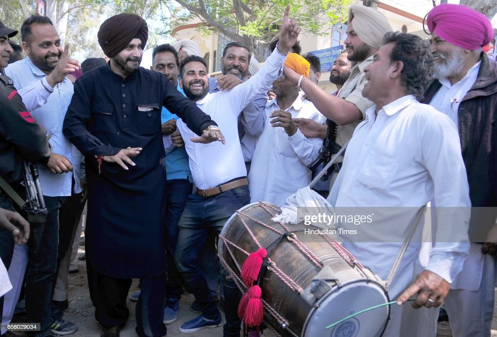 Punjab Local Bodies Minister Navjot Singh Sidhu performing bhangra with party workers during the thanksgiving visit to his constituency at Village...