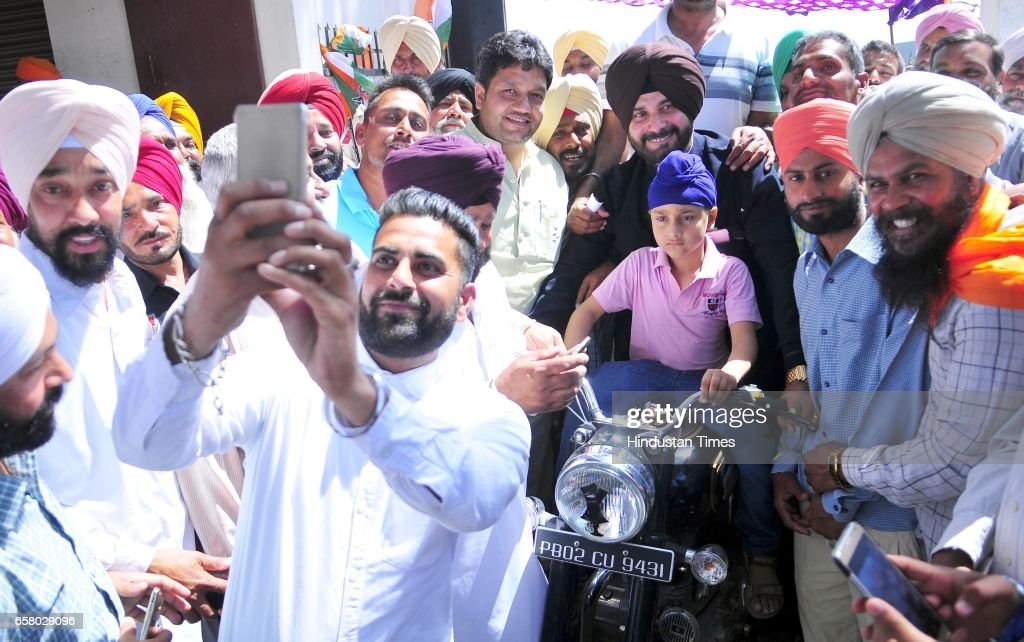 Punjab Local Bodies Minister Navjot Singh Sidhu riding a bike during the thanksgiving visit to his constituency at Village Mudhal on March 26 2017 in.