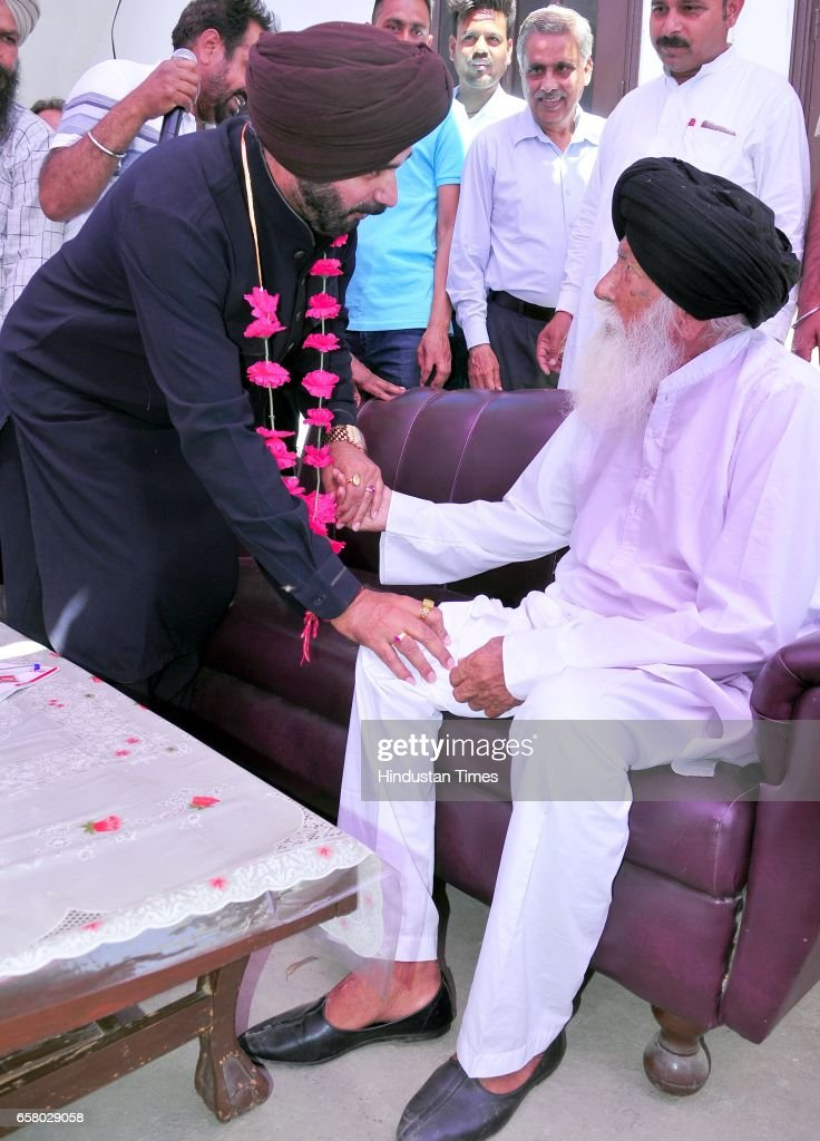 Punjab Local Bodies Minister Navjot Singh Sidhu touches the feet of an old man during the thanksgiving visit to his constituency at Village Mudhal on.