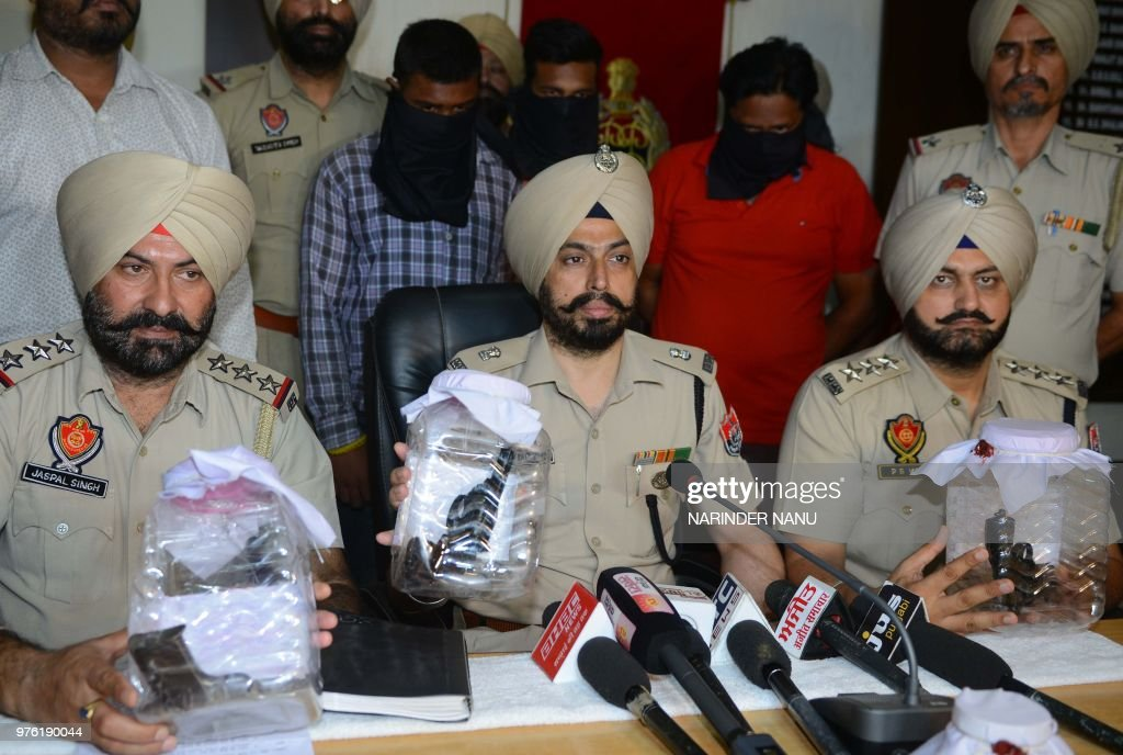 Punjab Police officers pose with 3 guns in front of three alleged culprits Akash Sandhu Danesh Sandhu and Ranjit Singh during a press conference in...