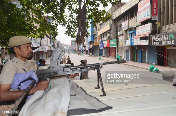 Punjab police personnel stand alert outside closed shops at Hall bazaar during a shutdown call given by radical sikh organizations Dal Khalsa on the...