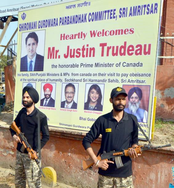 Punjab Police personnel stand guard in front of welcom hoarding installed by SGPC outside hall gate on the eve of visit of Canadian Prime Minister...