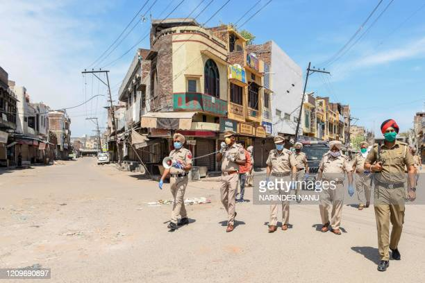 Punjab police personnel wearing facemasks patrol on a deserted street during a government-imposed nationwide lockdown as a preventive measure against...