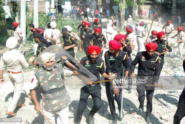 Punjab policemen chase away protestors after stones were pelted on them by angry protestors as they prepare for the resumption of railway services...