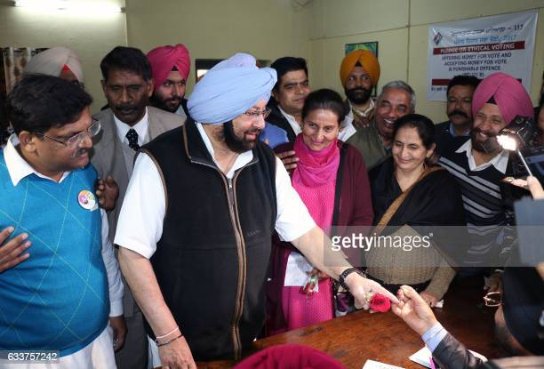 Punjab Pradesh Congress Committee President Amarinder Singh casts his vote for the 2017 assembly elections surrounded by supporters in Patiala on...