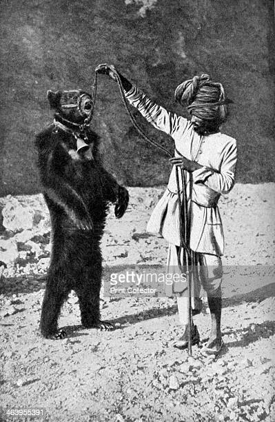Punjabi native with a dancing bear, India, 1922. From Peoples of All Nations, Their Life Today and the Story of Their Past, volume IV: Georgia to...