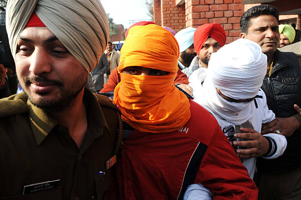 Punjabi Special Narcotics Cell police escort suspected smugglers Ranjinder Singh and Baljit Singh to an appearance in court in Amritsar on January 21.