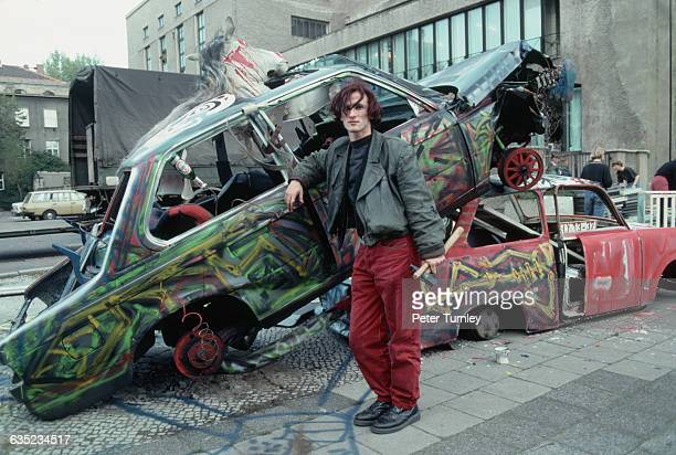 A punk artist poses with his sculpture of two wrecked cars with a bloody horses head emerging from the sunroof of one in East Berlin