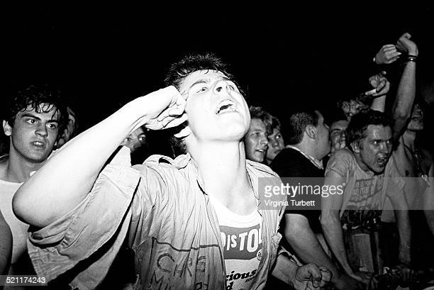 A punk fan in a Sex Pistols tshirt shouts from the audience while the Ruts perform at a Rock Against Racism concert the Rainbow Theatre London 13...