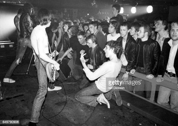 Punk fans in the audience crowd over the front of the stage and play air guitar as Joey Ramone and Johnny Ramone of The Ramones perform at Eric's...