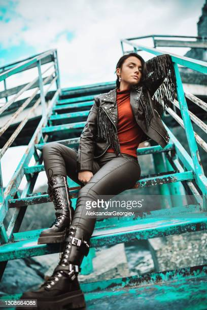 punk female in leather pants and high boots with fringed jacket sitting on staircase - punk music stock pictures, royalty-free photos & images