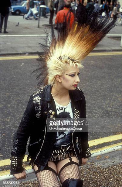 A punk girl with a large mohican leather jacket and fishnet stockings and suspenders King's Road Chelsea London UK 1984