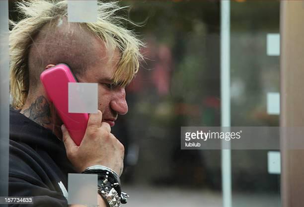 Punk man in Deutsche Telekom telephone box Berlin, Germany