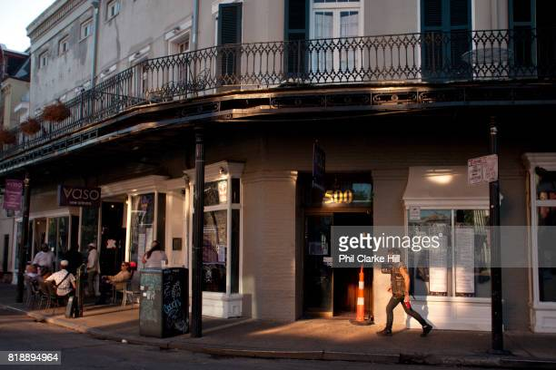 A punk man walks down Frenchman street in the afternoon light past jazz venues New Orleans Louisiana USA