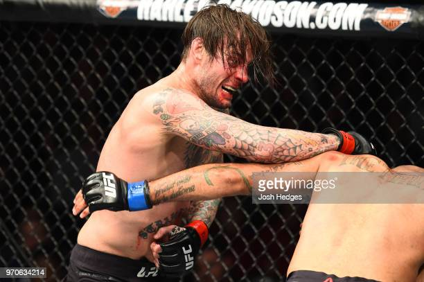 CM Punk punches Mike Jackson in their welterweight fight during the UFC 225 event at the United Center on June 9 2018 in Chicago Illinois