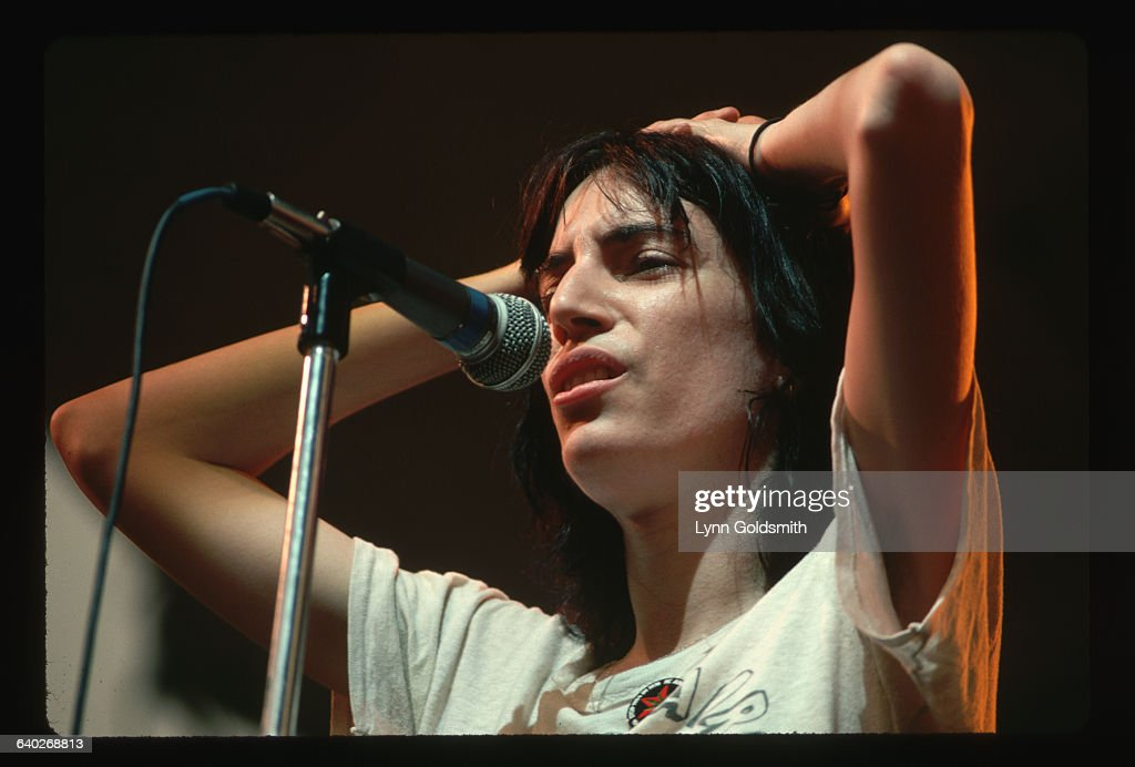Punk rock singer and poet Patti Smith sings with her hands on her head.