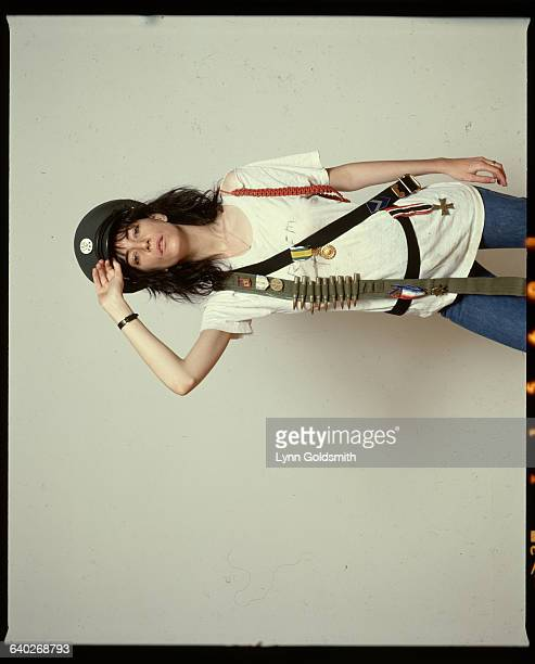 Punk rock singer and poet Patti Smith wears an ammunition belt and military decorations over a white Tshirt