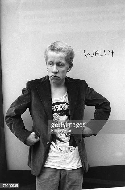 A Punk Rocker in the Kings Road Chelsea wearing a fashionable Roxy Punks Rule OK God Save the Queen white tshirt and standing next to graffiti that...