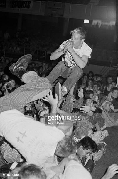 A punk singer crowd surfing above the audience at a concert starring punk rock bands Decry and Code of Honor