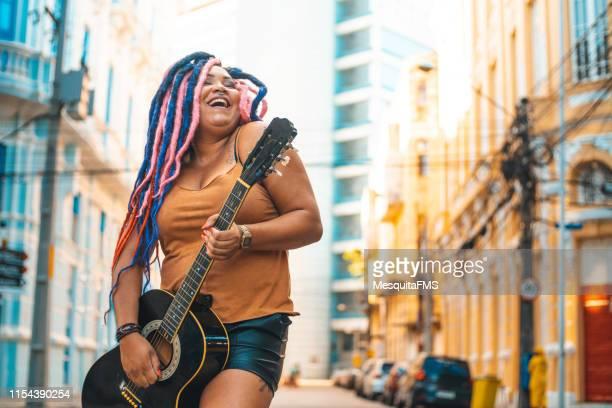 mulher do punk que joga a guitarra acústica - fashion show - fotografias e filmes do acervo