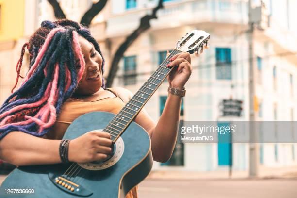 punk woman playing guitar outdoors - arte, cultura e espetáculo imagens e fotografias de stock