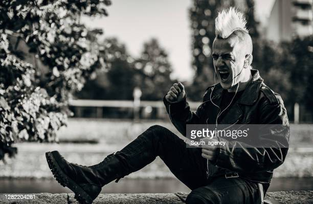 punker listening music on headphones and shouting on the street - mohawk stock pictures, royalty-free photos & images